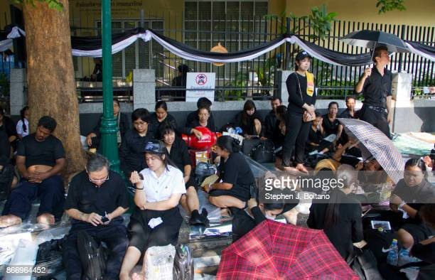 People wait close to Sanam Luang where the funeral and cremation of the late King of Thailand Bhumibol Adulyadej