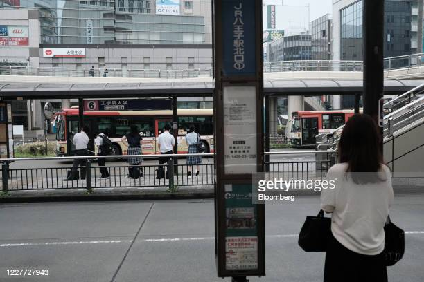 People wait for a bus at a bus stop at Hachioji Station in Hachioji City, Tokyo, Japan on Wednesday, July 22, 2020. Japans push to help revive its...