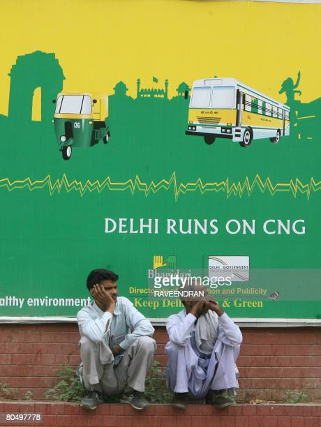 People wait for a bus in front of a bill board of Compressed Natural Gas for buses and autorickshaws in New Delhi on April 3 2008 The mandatory use...