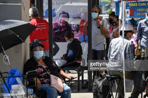 People wait for a bus in the largely Latino neighborhood of East Los Angeles August 7 2020 in Los Angeles California during the coronavirus pandemic...
