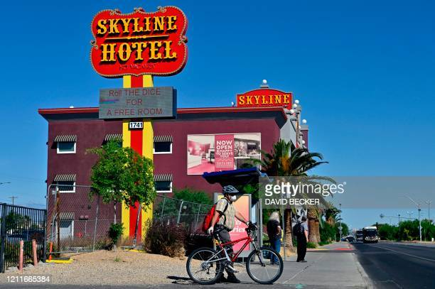 People wait for a bus near the Skyline Hotel Casino on May 2 2020 in Henderson Nevada as Nevada Governor Steve Sisolak announced that he is looking...