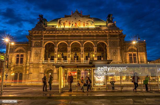 People wait for a city tram in front of the litup Wiener Staatsoper Vienna's State Opera building during the twilight in the city center of Vienna on...