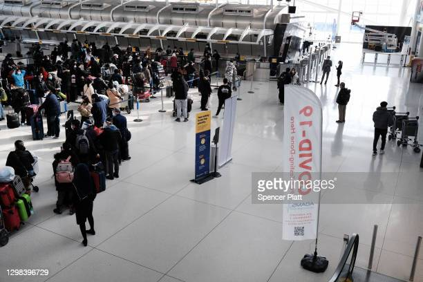 People wait for a flight at an international terminal at John F. Kennedy Airport on January 25, 2021 in New York City. In an effort to further...