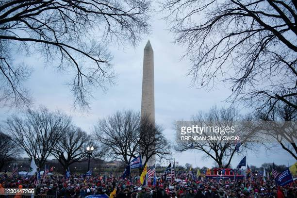 People wait for a rally of supporters of US President Donald Trump challenging the results of the 2020 US Presidential election on the Ellipse...