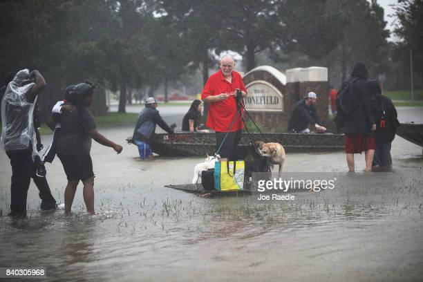 People wait for a rescue boat as they flee their homes after the area was inundated with flooding from Hurricane Harvey on August 28 2017 in Houston...
