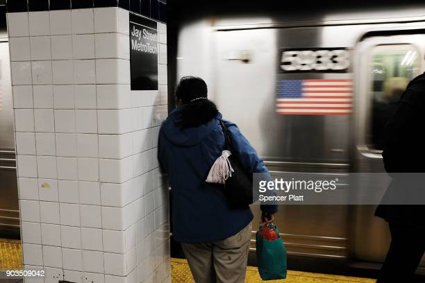 People wait for a subway at a stop in Brooklyn on January 10 2018 in New York City The New York City subway system which opened in 1904 and is the...