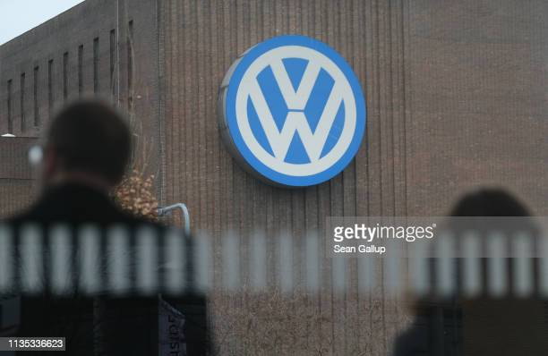 People wait for a train as the power station of the Volkswagen factory stands behind on March 12, 2019 in Wolfsburg, Germany. Volkswagen CEO Herbert...