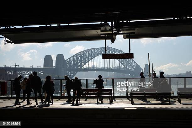 People wait for a train at Circular Quay near the harbour in Sydney on July 5 2016 Australia's central bank on July 5 held interest rates steady at...