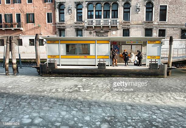 People wait for a Vaporetto at a waterbus stop where the canal is partially frozen on February 13 2012 in Venice Italy Italy like most of Europe is...