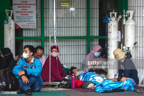 People wait for admission outside the emergency ward of a hospital tending to Covid-19 coronavirus patients in Surabaya on July 11 as Indonesia faces...