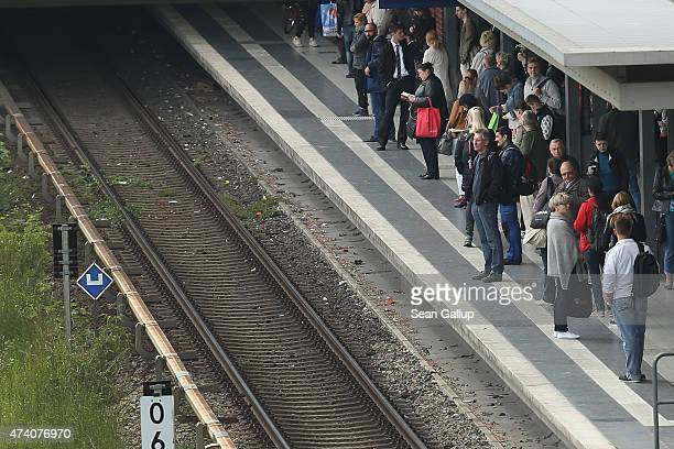 People wait for an S-Bahn commuter train during the first full day of a railway strike by the GDL train engineers' union on May 20, 2015 in Berlin,...