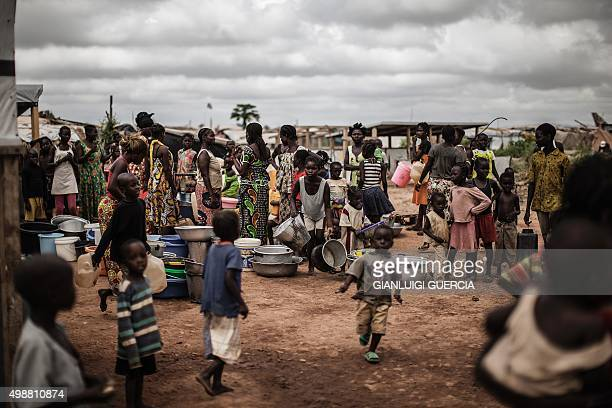 People wait for daily water distribution at the Mpoko Internally Displaced People camp in Bangui on November 26 ahead of a historical visit by the...