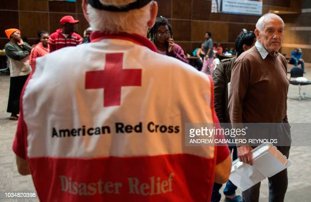 People wait for food inside an American Red Cross evacuation shelter in Chapel Hill North Carolina on September 17 2018 Catastrophic floods raised...