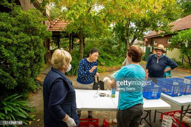 People wait for food items at St Paul's Anglican Church in Burwood on March 24 2020 in Sydney Australia The Parish Pantry provides food for the...