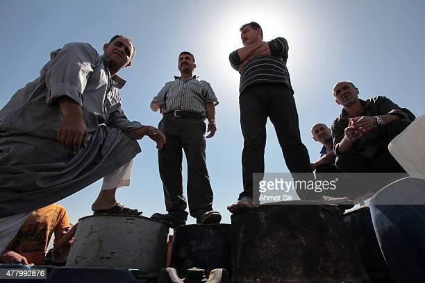 People wait for gas in a gas station in Tal Abyad, Syria. June 19, 2015. Kurdish fighters with the Kurdish People's Protection Units, or YPG took...