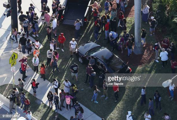 People wait for loved ones as they are brought out of the Marjory Stoneman Douglas High School after a shooting at the school that reportedly killed...