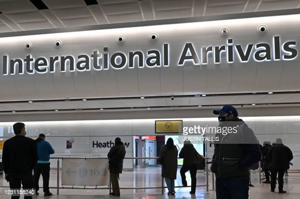 People wait for passengers at one of the International Arrivals halls at London Heathrow Airport in west London on February 14, 2021 . - A new 10-day...