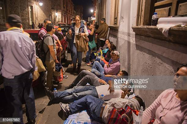 People wait for Pope Francis on a street of Morelia Michoacan Mexico on February 15 2016 Pope Francis reached out to Mexico's longmarginalized...