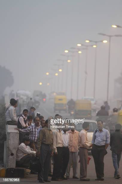 People wait for public transportation amid a blanket of smog caused by a mixture of pollution and fog at NCR region on November 7 2012 in New Delhi...