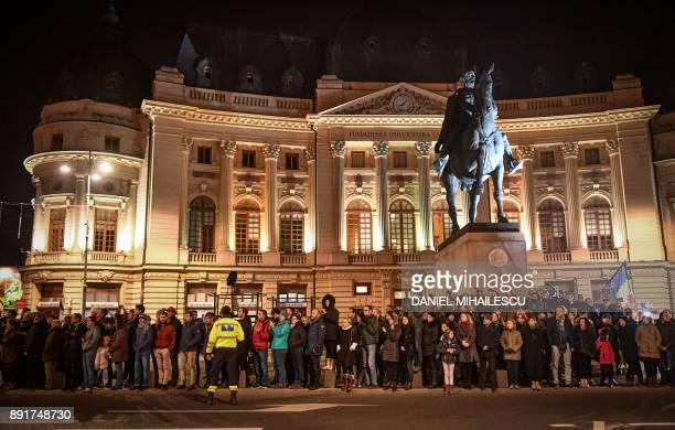 People wait for the arrival of the coffin of King Michael I of Romania on December 13 2017 outside the former Royal Palace that houses the National...
