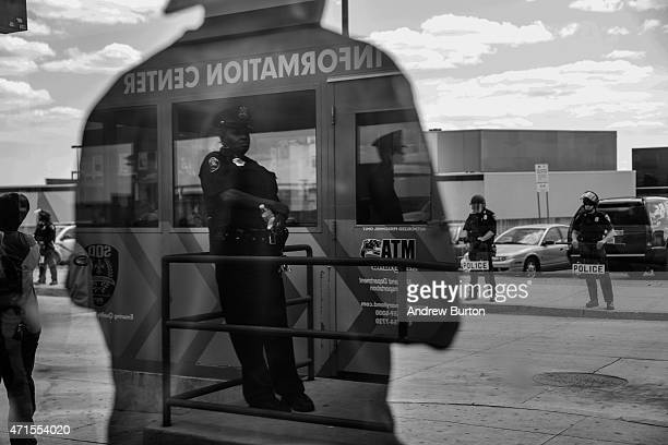 People wait for the bus at the Mondawmin Station while police secure Mondawmin Mall on April 29, 2015 in Baltimore, Maryland. Mondawmin Mall was...