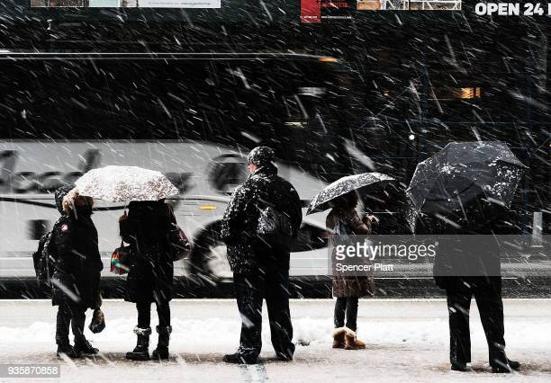 People wait for the bus in the snow on March 21 2018 in New York City New York City and much of New England has experienced four winter storms in...