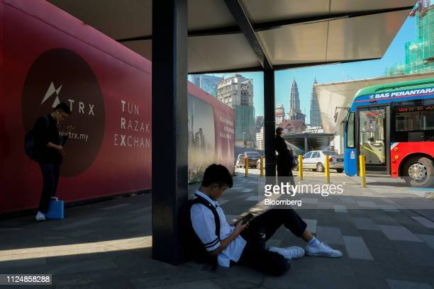 People wait for the bus near the site of the under construction Exchange TRX precinct in Kuala Lumpur Malaysia on Tuesday Feb 12 2019 The project has...