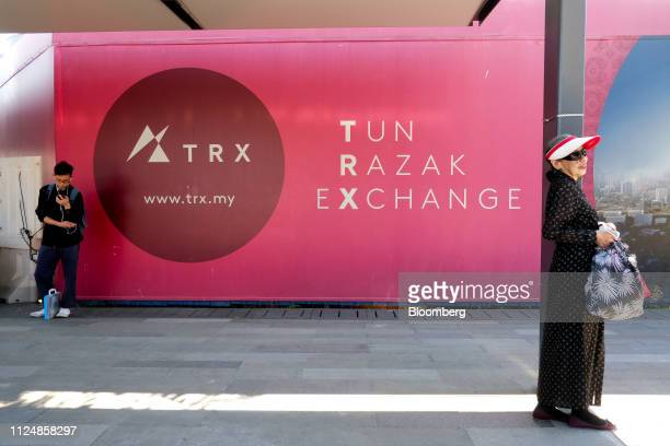 People wait for the bus next to a billboard for the under construction Exchange TRX precinct in Kuala Lumpur Malaysia on Tuesday Feb 12 2019 The...