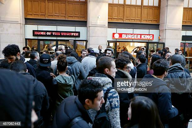 People wait for the opening of a Burger King store at Saint-Lazare railway station in Paris, on December 16, 2013. It is the fourth Burger King store...