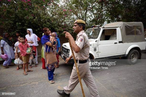 People wait for the police permission to let them go to their home due to an encounter between the Special Cell and a gang of criminals in the...