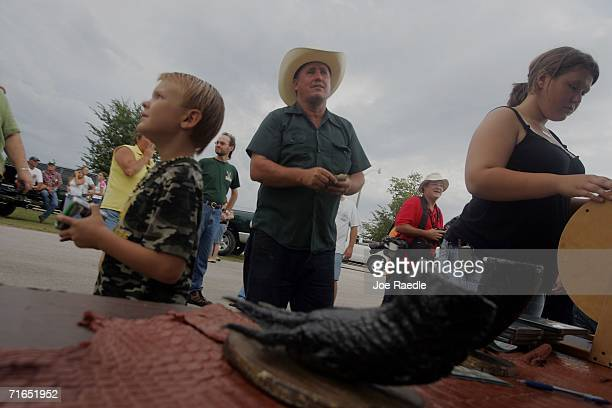 People wait for the raffle drawing to see who wins an alligator head or foot before hunters drop their airboats into Lake Okeechobee on the first day...