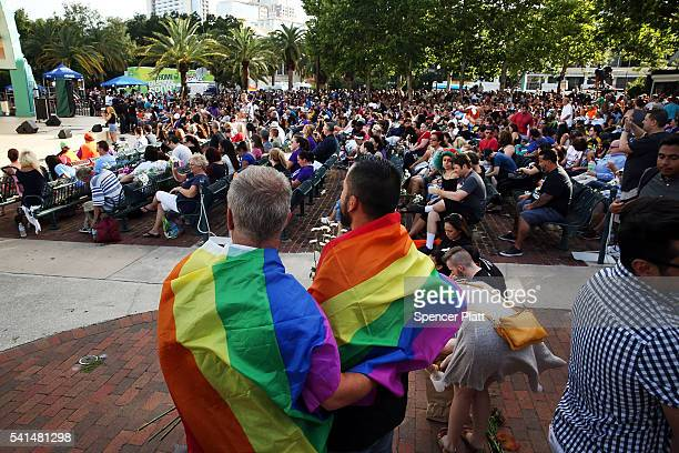 People wait for the start of a memorial service on June 19 2016 in Orlando Florida Thousands of people are expected at the evening event which will...