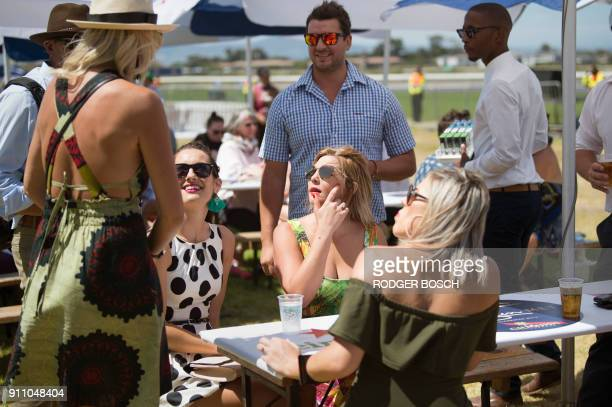 People wait for the start of the Met horse race at Kenilworth race track on January 27 in Cape Town The Met is one of South Africa's premier horse...