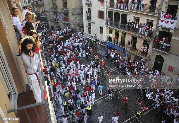 People wait for the start of the seventh bullrun of the San Fermin Festival in Pamplona northern Spain on July 13 2014 The festival is a symbol of...