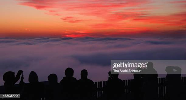 People wait for the sunrise above the sea of clouds at Mount Takatani on October 29 2014 in Miyoshi Hiroshima Japan