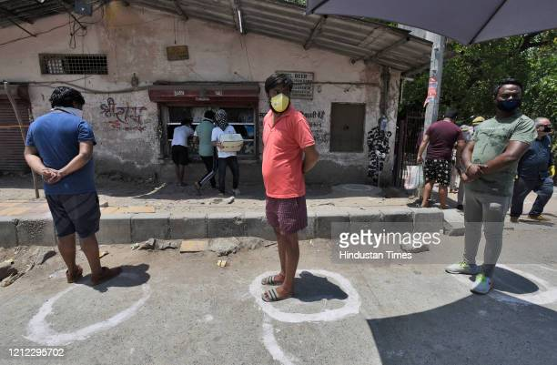 People wait for their turn in a queue to buy alcohol outside a liquor shop after Delhi government issued e-tokens, specifying stores and timings, at...