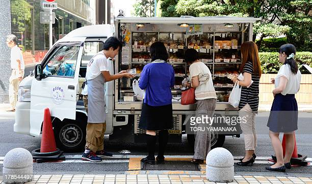 People wait for their turn in line to buy bread from a street vendor in Tokyo on August 30 2013 Japan's consumer prices rose at their fastest pace in...