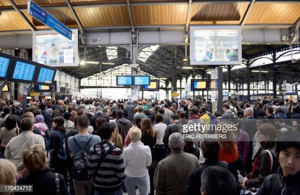People wait for trains at the Saint Lazare train station during a strike by French SNCF railway company employees on June 13 in Paris The strike was...