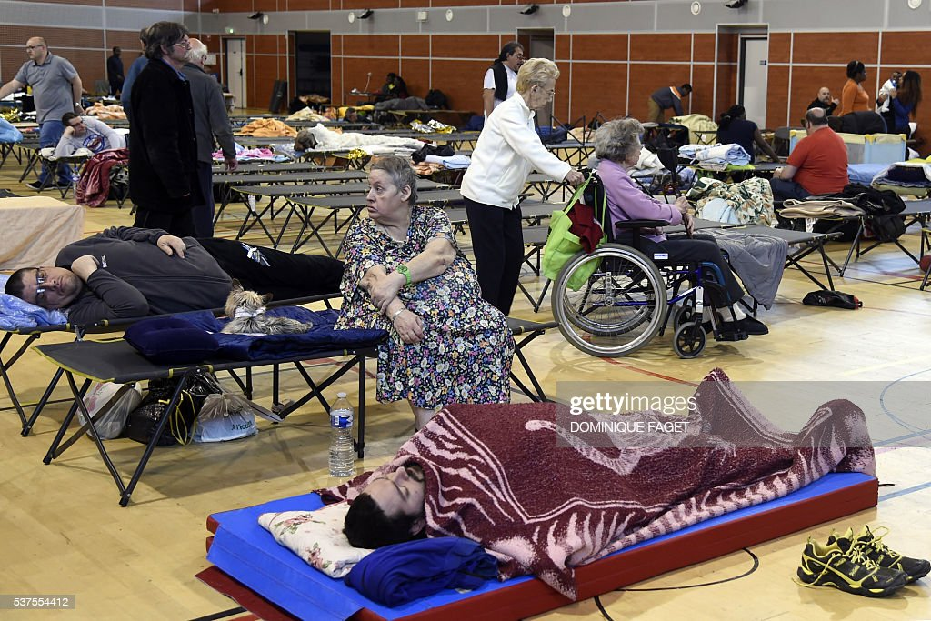 People wait in a gymnasium of Nemours,some 80km south of