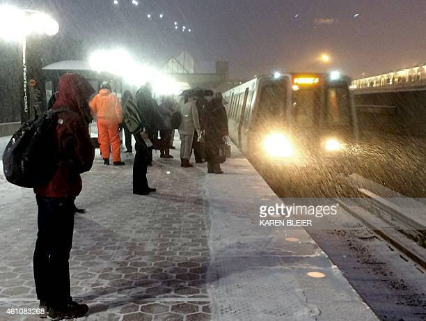 People wait in a heavy snow for the train to arrive January 6 2015 in Vienna Virginia The first significant snowfall of the year wrecked havoc on the...