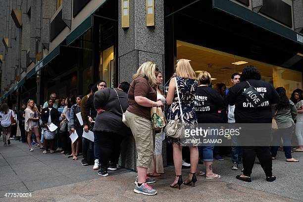 People wait in a line to buy EL James's new book Grey Fifty Shades of Grey as Told by Christian outside the Barnes and Noble store on Fifth Avenue in...