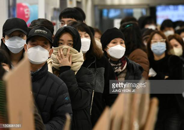 People wait in a line to buy face masks at a retail store in the southeastern city of Daegu on February 25, 2020. - South Korea reported 60 more...