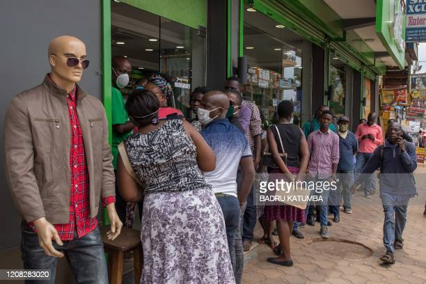 People wait in a line to enter a pharmacy in Kampala Uganda on March 26 after Ugandan President Yoweri Museveni directed the public to stay home for...