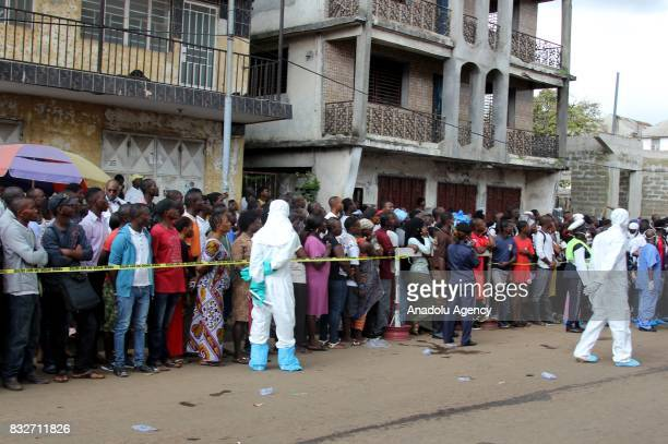 People wait in a line to identify their relatives' bodies at Connaught hospital after landslide struck the capital of the west African state of...
