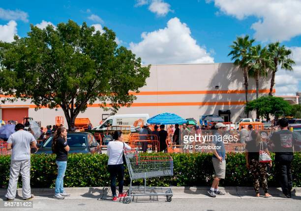 People wait in a line to purchase supplies outside a Home Depot store in Miami Florida as they prepare for Hurricane Irma on September 7 2017 Miami...