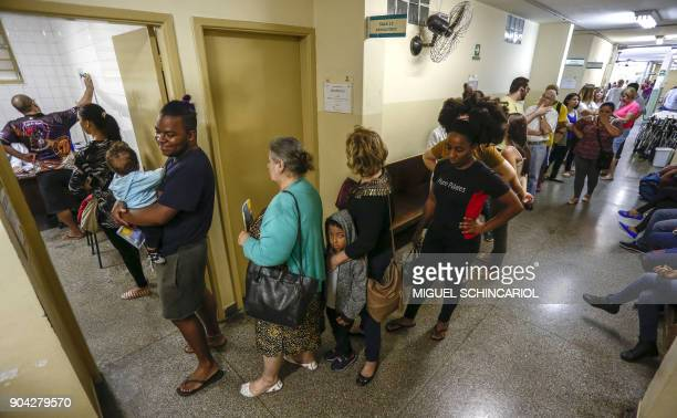 People wait in a long line to be vaccinated against yellow fever at an outpatient clinic in Sao Paulo Brazil on January 12 2018 Brazil stepped up...
