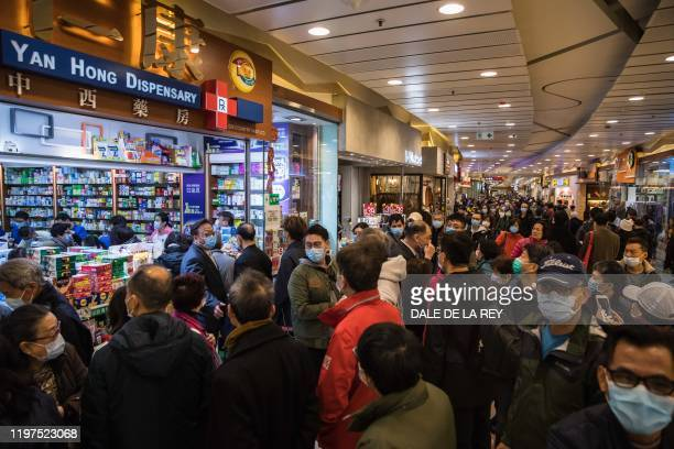 TOPSHOT People wait in a queue and gather outside outside a pharmacy selling masks in Hong Kong on January 30 as a preventative measure after a virus...