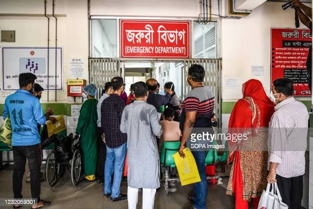 People wait in a queue for serial numbers without keeping social distance to test for the COVID-19 coronavirus at Mugda Medical College and Hospital....