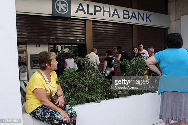 People wait in a queue in front of a bank's ATM to withdraw their cash in Athens Greece on June 28 2015 Greeks are anxious about whether the European...