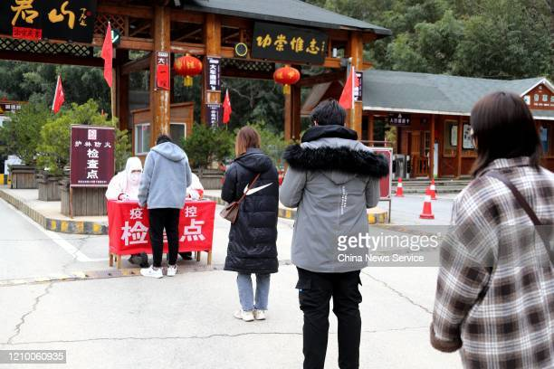 People wait in a queue to check in identity information at entrance of Laojunshan Scenic Spot amid novel coronavirus outbreak on March 3, 2020 in...